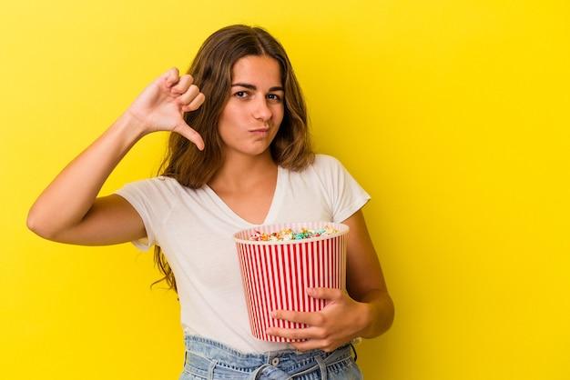 Jonge kaukasische vrouw die popcorns houdt die op gele achtergrond wordt geïsoleerd die een afkeergebaar toont, duim omlaag. onenigheid begrip.