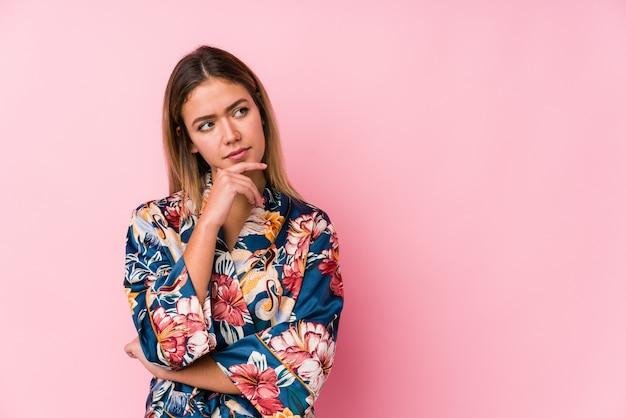 Jonge kaukasische vrouw die pyjama's draagt die zijdelings met twijfelachtige en sceptische uitdrukking kijken.