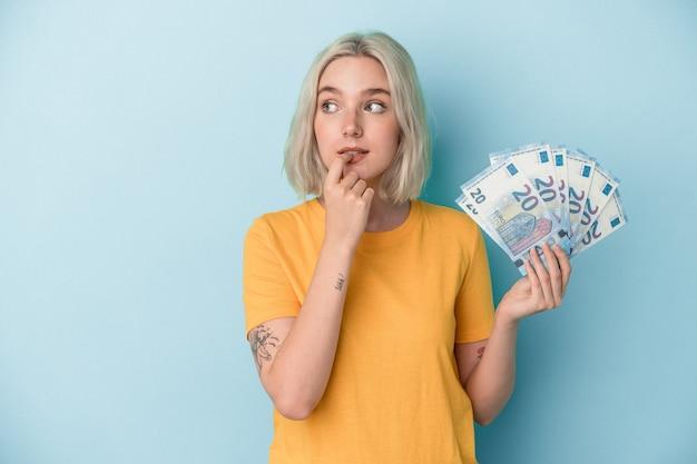 Jonge kaukasische vrouw die rekeningen houdt die op blauwe achtergrond worden geïsoleerd ontspannen denkend over iets dat een exemplaarruimte bekijkt.