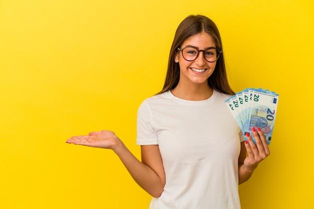 Jonge kaukasische vrouw die rekeningen houdt die op gele achtergrond worden geïsoleerd die een exemplaarruimte op een palm tonen en een andere hand op taille houden.