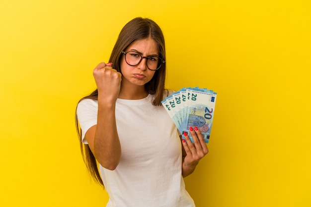 Jonge kaukasische vrouw die rekeningen houdt die op gele achtergrond worden geïsoleerd die vuist tonen aan camera, agressieve gezichtsuitdrukking.