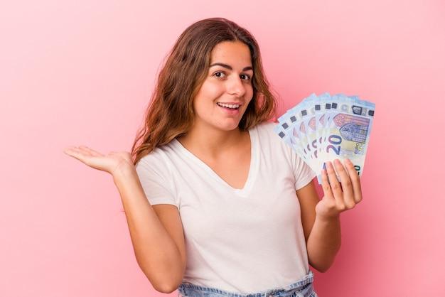 Jonge kaukasische vrouw die rekeningen houdt die op roze achtergrond worden geïsoleerd die een exemplaarruimte op een palm tonen en een andere hand op taille houden.