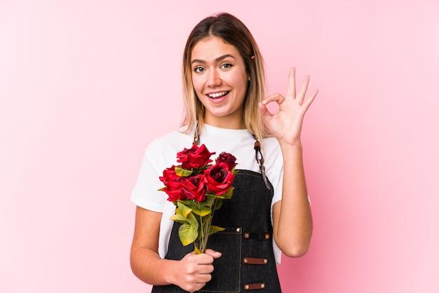Jonge kaukasische vrouw die rozen geïsoleerd vrolijk en zeker houdt die ok gebaar toont.