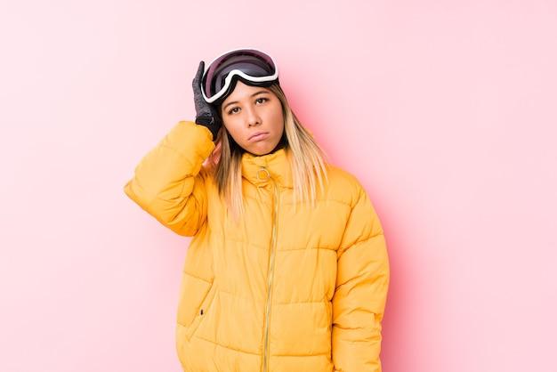 Jonge kaukasische vrouw die skikleren in een roze muur draagt die geschokt wordt, heeft zij belangrijke vergadering herinnerd.