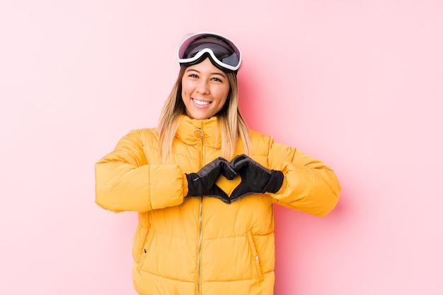Jonge kaukasische vrouw die skikleren in roze draagt die en een hartvorm glimlachen tonen