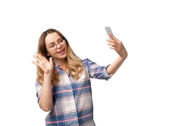 Jonge kaukasische vrouw die smartphone, apparaten, gadgets gebruikt die op witte studioachtergrond worden geïsoleerd.