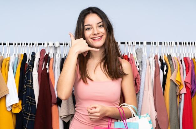 Jonge kaukasische vrouw die sommige kleren in een opslag koopt die telefoongebaar maakt
