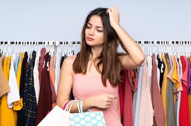 Jonge kaukasische vrouw die sommige kleren in een opslag koopt die twijfels heeft terwijl het hoofd krabben