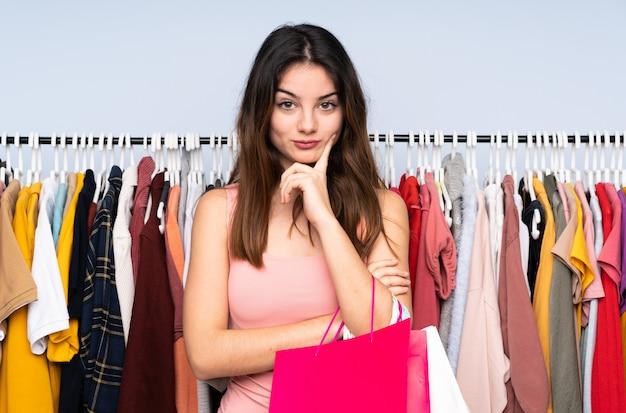 Jonge kaukasische vrouw die sommige kleren in een opslag koopt en voorzijde kijkt