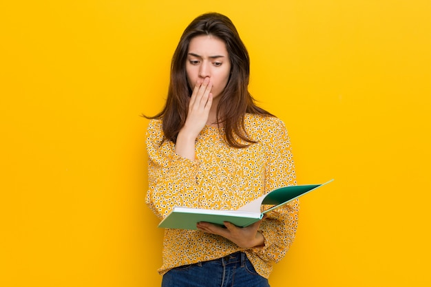 Jonge kaukasische vrouw die sommige notitieboekjes houdt