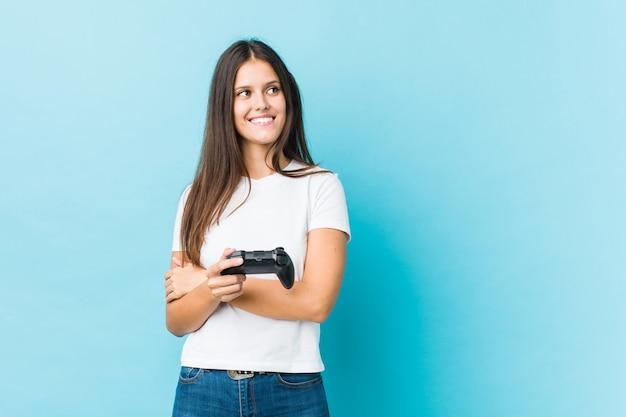 Jonge kaukasische vrouw die spelcontrolemechanisme glimlachen houden zeker met gekruiste wapens.