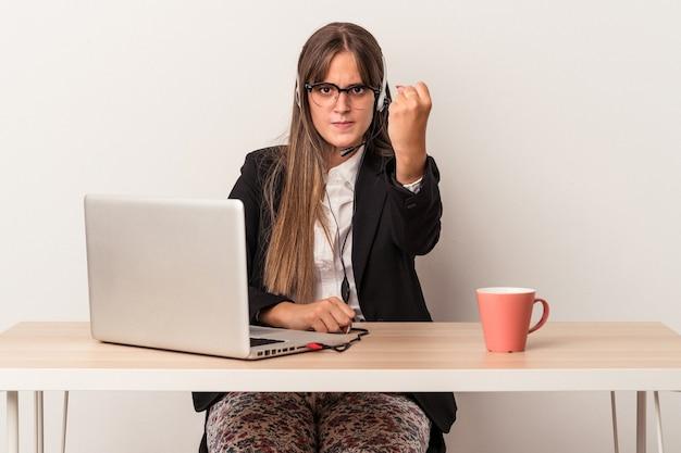 Jonge kaukasische vrouw die telewerken doet die op witte achtergrond wordt geïsoleerd die vuist toont aan camera, agressieve gezichtsuitdrukking.