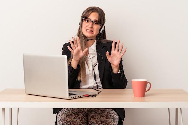 Jonge kaukasische vrouw die telewerken doet die op witte achtergrond wordt geïsoleerd en iemand afwijst die een gebaar van walging toont.
