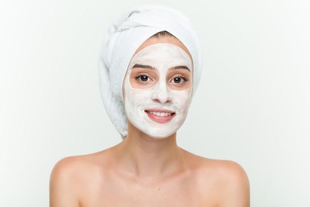 Jonge kaukasische vrouw die van offacial maskerbehandeling geniet