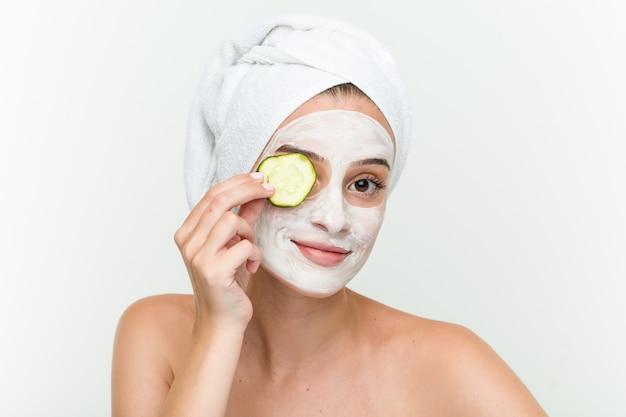 Jonge kaukasische vrouw die van offacial maskerbehandeling met komkommer geniet