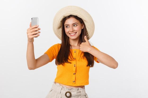 Jonge kaukasische vrouw die van selfie met zich genieten geïsoleerd op het witte concept van de de zomerreis.