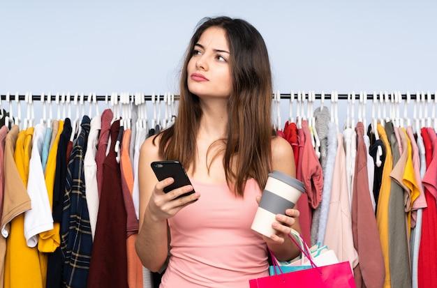 Jonge kaukasische vrouw die wat kleren in een koffie van de opslagholding kopen om weg te halen en mobiel terwijl het denken van iets