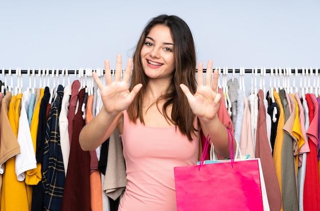 Jonge kaukasische vrouw die wat kleren in een opslag koopt die negen met vingers telt