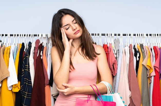 Jonge kaukasische vrouw die wat kleren in een opslag met hoofdpijn koopt