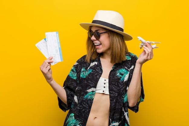 Jonge kaukasische vrouw die zeer gelukkige luchtkaartjes houdt.
