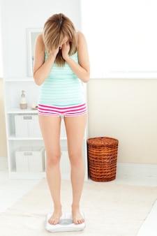 Jonge kaukasische vrouw die zich op een schaal in de badkamer