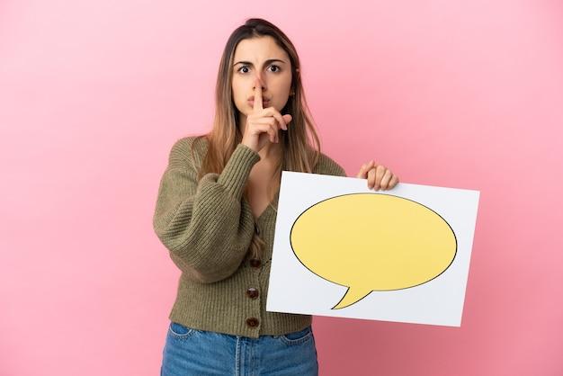 Jonge kaukasische vrouw geïsoleerd die een plakkaat met het pictogram van de toespraakbel houdt die stiltegebaar doet