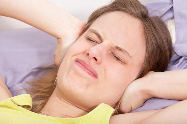 Jonge kaukasische vrouw in bed met hoofdpijndepressie