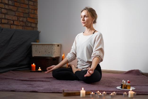 Jonge kaukasische vrouw in de positie van yogalotusbloem binnen binnen