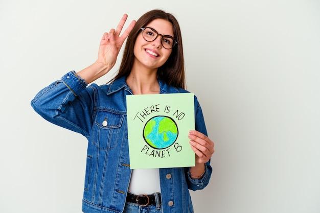 Jonge kaukasische vrouw met een plakkaat voor veganistisch leven geïsoleerd op een witte achtergrond verward, voelt zich twijfelachtig en onzeker.