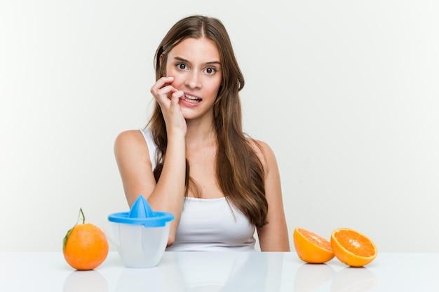 Jonge kaukasische vrouw met een sinaasappel juicer bijtende vingernagels