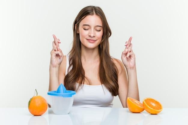 Jonge kaukasische vrouw met een sinaasappelpers die vingers kruisen voor het hebben van geluk