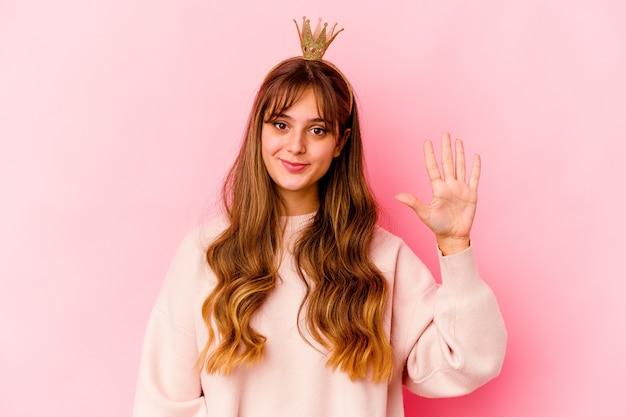 Jonge kaukasische vrouw met geïsoleerde prinseskroon glimlachend vrolijk tonend nummer vijf met vingers.