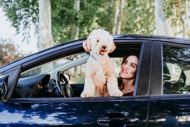 Jonge kaukasische vrouw met haar poedelhond in een auto