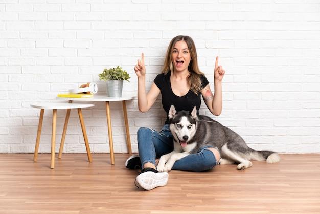 Jonge kaukasische vrouw met hond over geïsoleerde muur