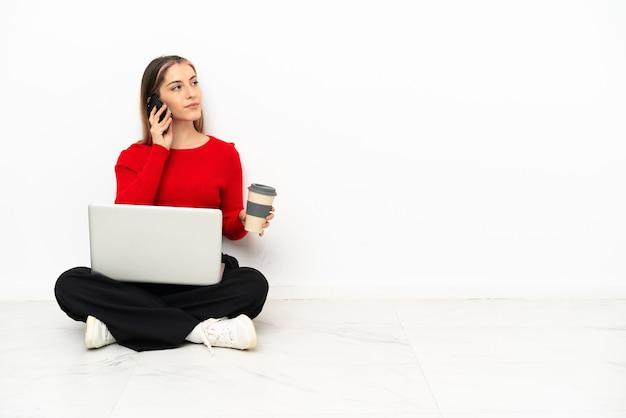 Jonge kaukasische vrouw met laptop zittend op de vloer met koffie om mee te nemen en een mobiel