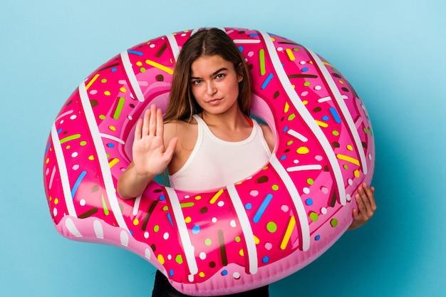 Jonge kaukasische vrouw met opblaasbare donut geïsoleerd op blauwe achtergrond permanent met uitgestrekte hand weergegeven: stopbord, voorkomen dat u.