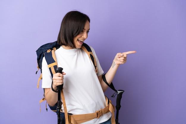 Jonge kaukasische vrouw met rugzak en trekkingstokken die op blauwe wijzende vinger naar de kant worden geïsoleerd en een product voorstellen