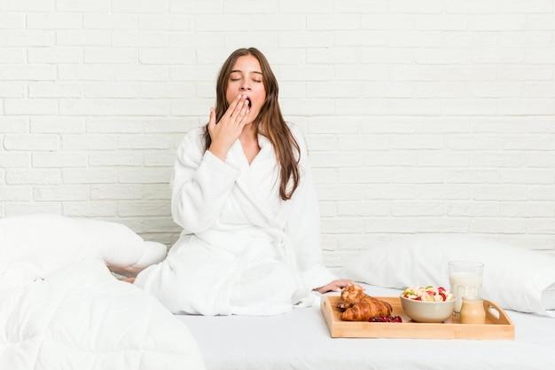 Jonge kaukasische vrouw op bed geeuwt het tonen van een vermoeid gebaar die mond behandelen met hand.