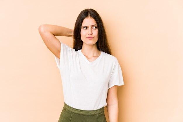Jonge kaukasische vrouw op beige muur aanraken achterkant van hoofd, denken en het maken van een keuze.