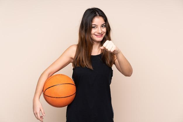 Jonge kaukasische vrouw op beige muur basketbal spelen en trots op zichzelf