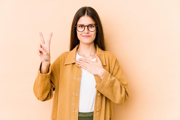 Jonge kaukasische vrouw op beige muur die een eed afleggen, die hand op borst zetten.