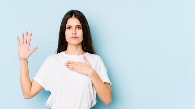 Jonge kaukasische vrouw op blauwe muur die een eed afleggen, die hand op borst zetten.