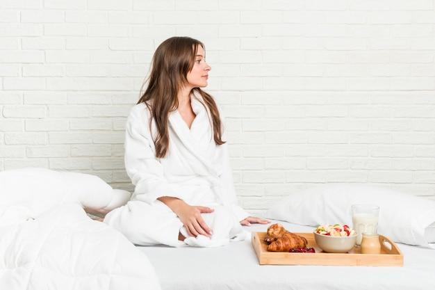 Jonge kaukasische vrouw op het bed dat links staart