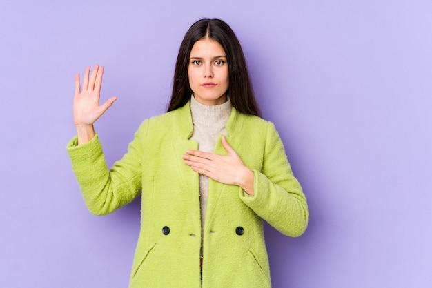 Jonge kaukasische vrouw op purpere muur die een eed afleggen, die hand op borst zetten.