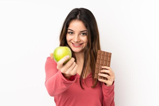 Jonge kaukasische vrouw op roze muur die een chocoladetablet in de ene hand en een appel in de andere