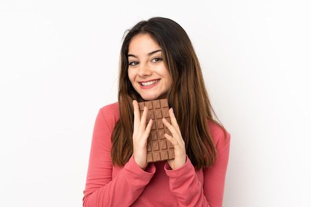 Jonge kaukasische vrouw op roze muur die een chocoladetablet nemen en gelukkig