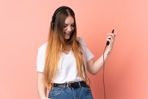 Jonge kaukasische vrouw op roze muur het luisteren muziek en het doen van gitaargebaar