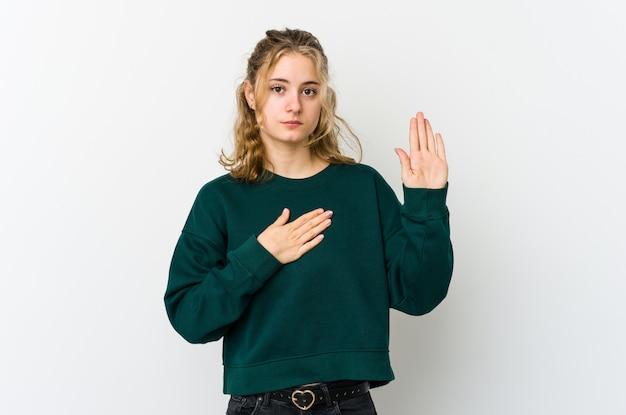 Jonge kaukasische vrouw op witte muur die een eed afleggen, die hand op borst zetten.