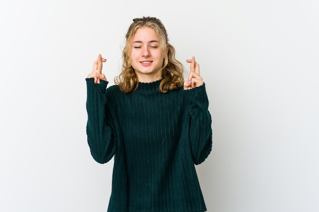 Jonge kaukasische vrouw op witte muur die vingers kruist