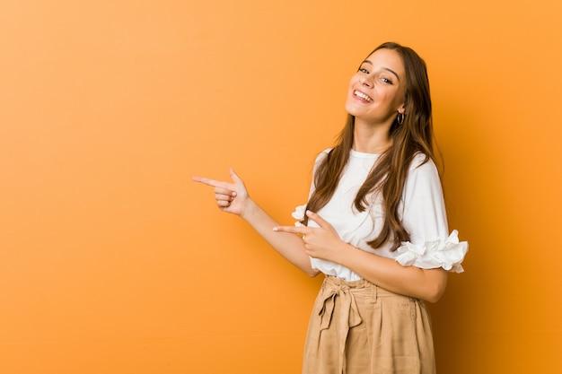 Jonge kaukasische vrouw opgewonden wijzend met weg wijsvingers.
